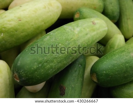 background of a heap of ripe juicy organic cooling china mini cucumber on display in rattan basket for sale at local farmer's market departmental store - stock photo