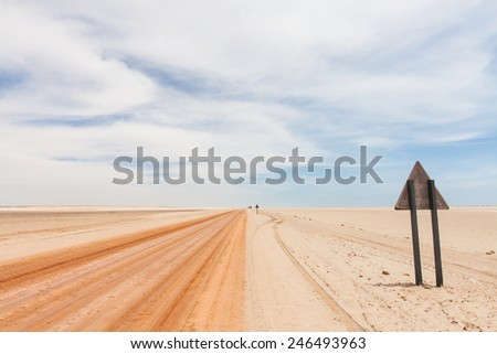 background of a red sandy desert road in the Namib and the backside of a warning triangle road sign, Skeleton coast National Park, Namibia, Africa - stock photo