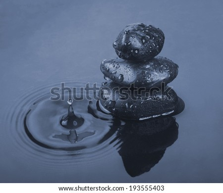 Background of a spa with black stones and dark water. - stock photo