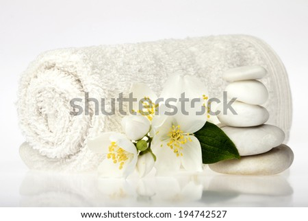 Background of a spa with pile of stones, towel and blossoms on a white background. - stock photo