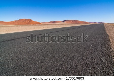 background of a tared road in front of the red dunes of the namibian Namib desert under a blue sky, Naukluft Park, Namibia, Africa - stock photo