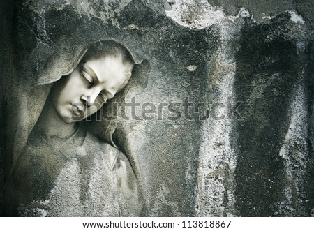 Background of an grungy dark wall with a beautiful detail face of a sculpture of a female saint - stock photo