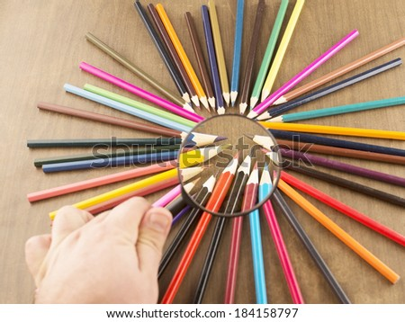 background of bunch colored pencils under magnifying on wood idea of concentration and attraction to nucleus center circle radius unity concept  leadership, community team focused on one goal - stock photo