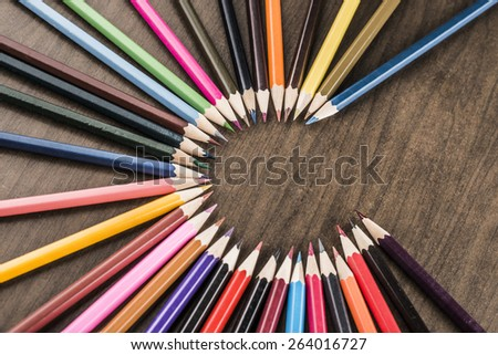 background of bunch of colored pencils on black paper The idea of concentration and attraction to nucleus center circle radius unity concept of leadership, community, the team focused on one goal - stock photo