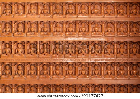Background of carved wall with many Buddha figures sitting in yoga position. Sandstone bas-relief in 12th century Jain temples of Jaisalmer Fort, Rajasthan, India. - stock photo