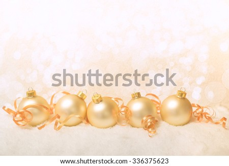 background of Christmas ornaments, curly ribbon and festive bokeh lighting with copy space for your holiday projects - stock photo