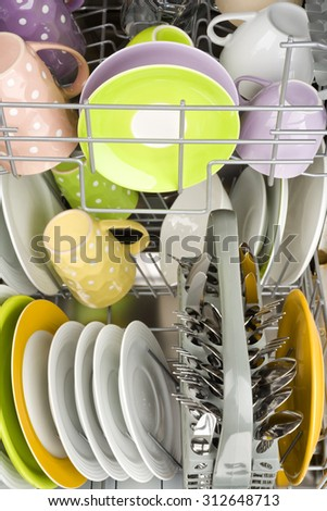 Background of clean dishes in dishwashing machine, front view - stock photo