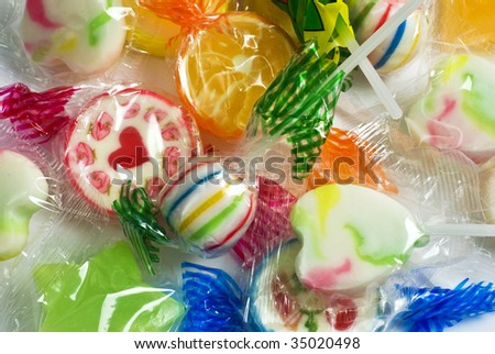 background of colorful, cellophane-wrapped lollipops - stock photo