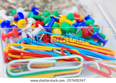 background of colorful stationery: staples and drawing pins - stock photo