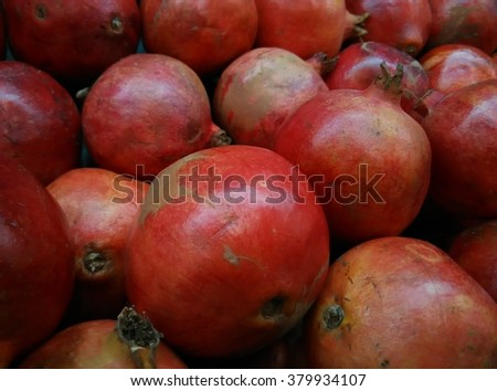 background of fresh organic ripe handpicked pomegranates from turkey on display at local farmer's market departmental store - stock photo