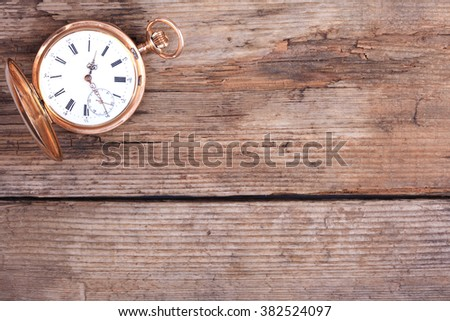 background of golden pocket watch on wooden surface - stock photo
