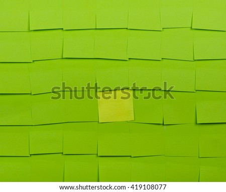 Background of green sticky notes. Yellow sticky note is among green sticky notes. - stock photo
