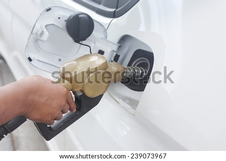 background of hand filling up car fuel - stock photo