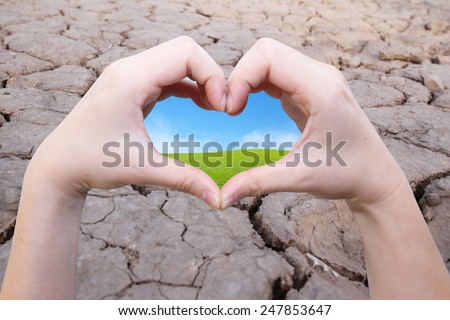 background of hand in heart shape with green field inside on the crack earth - stock photo