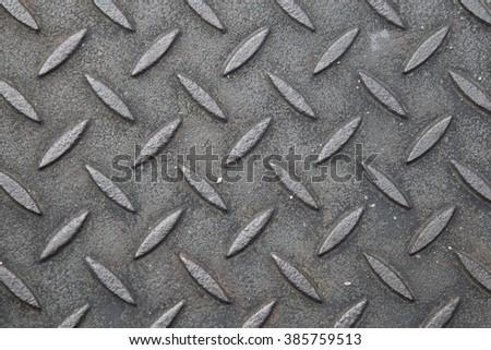 Background of metallic textures on sewer manhole. - stock photo