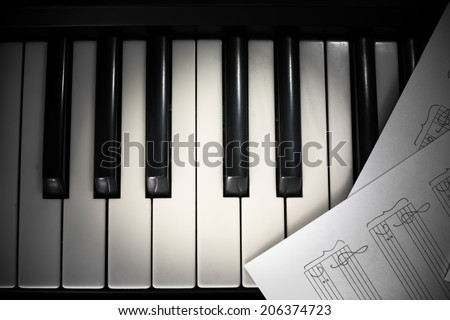 background of piano keyboard and notes with vignette - stock photo