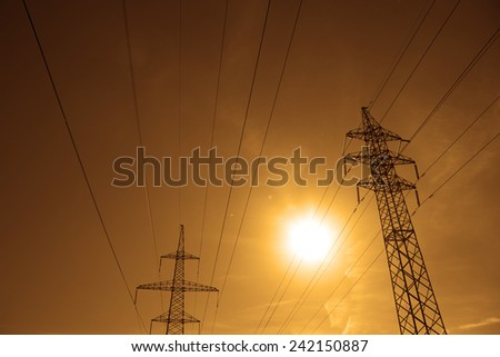 Background of Pylon and power lines at sunset with red sky with clouds and sun shine rays  - stock photo