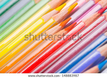 Background of rainbow coloured wooden pencil crayons arranged diagonally with a close up view of the tips - stock photo