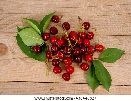 Background of ripe cherries. Pile of fresh and tasty cherries. Fresh cherries scattered on a wooden table. Top view. - stock photo