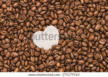 background of roasted coffe beans and a heart with copy space. Conceptual image of the love of coffee and great taste. - stock photo