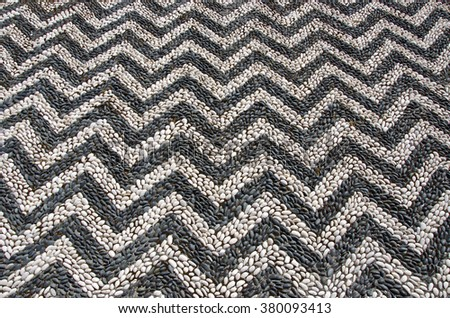 Background of round black and white pebble patterned sidewalk in Rhodes island, Greece on sunny day - stock photo
