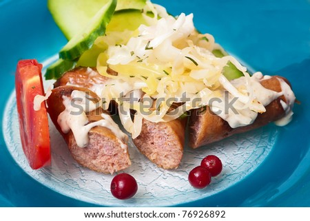 Background of sausage with vegetables on blue plat - stock photo