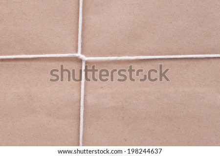 Background of white cardboard paper tied with twine - stock photo