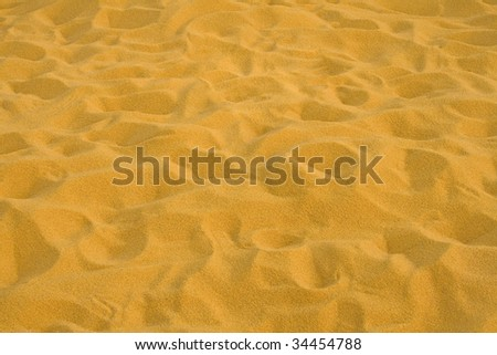 Background of yellow/orange sand in sunny day. - stock photo
