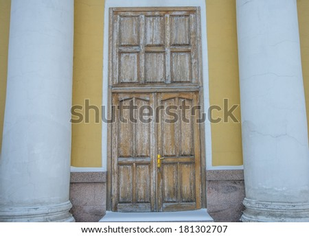 Background of yellow wall with two white column and monumental wooden old retro door in Russia - stock photo