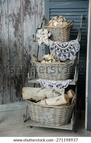 Background rustic veranda with a shelf with baskets and angels. Old decorations and wooden walls - stock photo