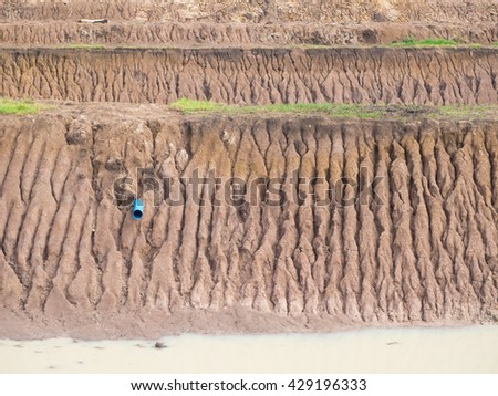 Background Soil coastal canal, which was rain water erosion, which has a plastic water pipe emerges. - stock photo