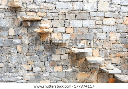Background texture of a decorative natural stone wall built from random hewn blocks using the dry-stone method of building without mortar with a diagonal pattern of raised steps - stock photo