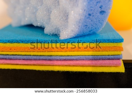 Background texture of a pile of vivid colorful new absorbent kitchen cloths stacked on a counter with a sponge, close up detail - stock photo