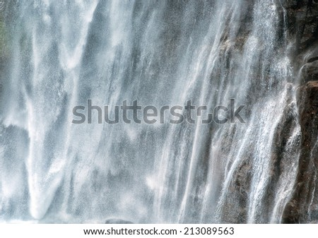 Background texture of a powerful torrent of white water cascading down a cliff in a mountain waterfall - stock photo