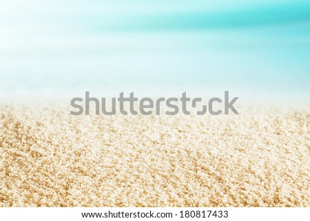 Background texture of golden sand on a deserted tropical beach on a beautiful hot summer day with a blue ocean and sky conceptual of travel, nature and vacations - stock photo