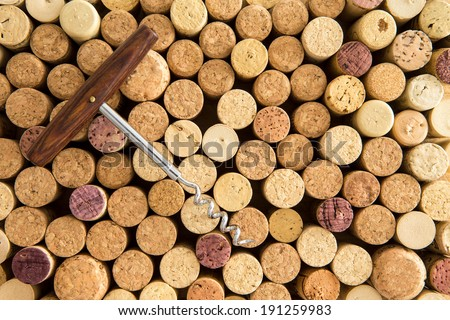 Background texture of neatly arranged corks and calassic wine bottle opener wine packed tightly together with their tops facing up to the camera forming a circular pattern - stock photo