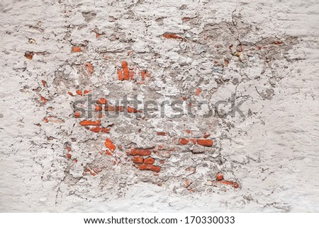 Background texture of old damaged brick wall with white stucco - stock photo