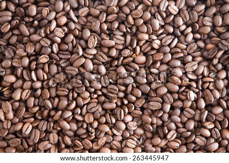 Background texture of roasted brown coffee beans ready for grinding for a fresh cup of aromatic coffee at breakfast, close up view from above - stock photo