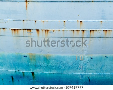 Background texture pattern of blue painted grungy steel hull of ocean ship close-up - stock photo