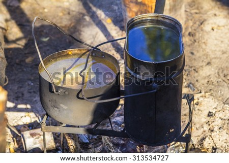 Background Two pot with water heated on the fire during a camping trip in the woods - stock photo