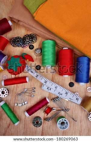 Background vertical with sewing items: buttons, colorful fabrics, material, measuring tape, bobbins, buttons, cloth, safety pins, needles, pincushion, thimble, spools of thread - stock photo