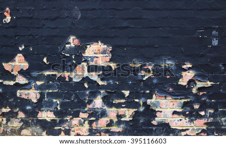 Background/ wallpaper - black flaking paint on an old brick wall. - stock photo