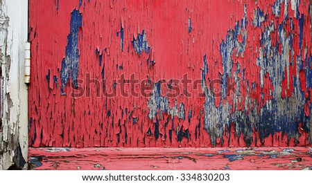 Background/ wallpaper - flaking red, blue and green paint at the bottom of a door. - stock photo