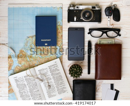 background - what to take for a trip. passport, phone, documents, car keys, map, camera, money, sunglasses, credit cards - stock photo