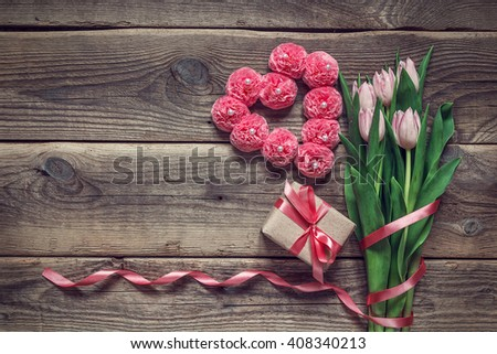 Background with a bouquet of tulips, gift box and a heart shape on old wooden boards. Place for text. Top view. - stock photo