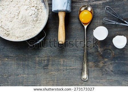 Background with baking ingredients - egg yolk, flour and rolling pin on wooden texture. Top view. - stock photo