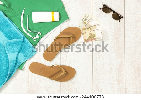 Background with beach supplies and foreign currency money on floorboard - stock photo