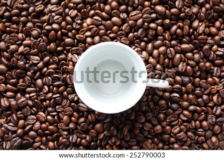Background with coffee beans and empty cup - stock photo