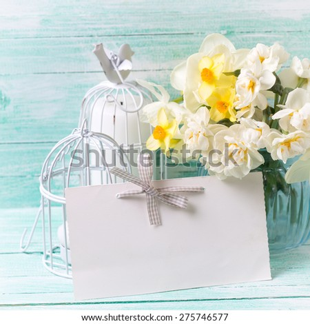 Background with colorful narcissus flowers in blue vase, candles  and empty tag for text on turquoise painted wooden planks. Selective focus. Place for text. Square image.  - stock photo
