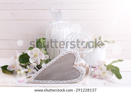 Background  with  decorative heart, tender apple blossom, candles in decorative bird cages in ray of light   on white painted wooden planks. Selective focus is on heart. - stock photo